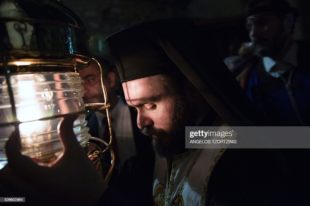An Orthodox priest holds up the 'Holy Fire' as worshippers gather during the Orthodox Easter ceremony at the Church of Metochi Panagiou Tafou in Athens, on April 30, 2015. Millions of Greeks flock to churches around the country this week to celebrate Easter, the country's foremost religious celebration. / AFP / ANGELOS