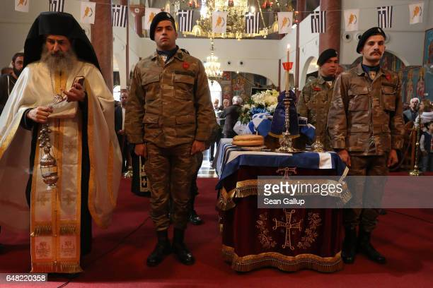 An Orthodox priest leads a funeral service as soldiers stand next to the small coffin that contains the remains of Georgiou Theodoulos Theodoulou on...