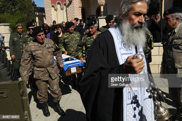 An Orthodox priest leads soldiers carrying the small coffin containing the remains of Georgiou Theodoulos Theodoulou at his funeral on March 5 2017...