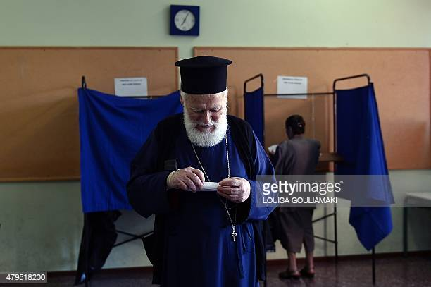 An Orthodox priest prepares to cast his ballot for the Greek referendum at a polling station in Athens on July 5 2015 Nearly 10 million Greek voters...