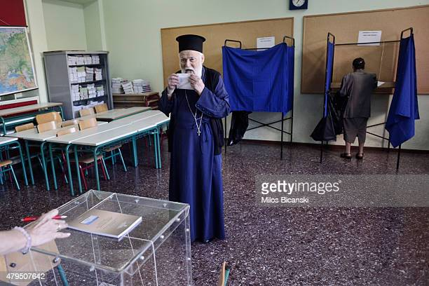 An Orthodox priest prepares to put a referendum vote in the ballot box at a school on July 5 2015 in Athens Greece The people of Greece are going to...