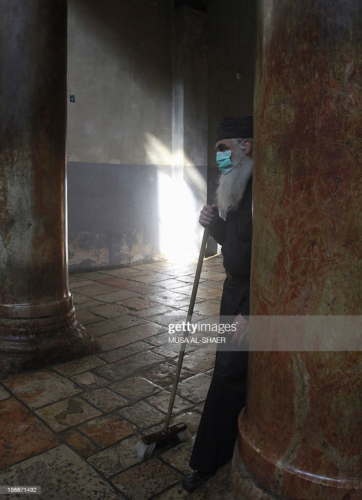 An Orthodox priest takes part in the cleaning of the Church of Nativity on January 2, 2013, in the West Bank town of Bethlehem. The sovereignty of the Church of the Nativity, traditionally believed to be the birthplace of Jesus Christ, is shared by the Christian denominations, who also share the annual cleaning responsibilities.