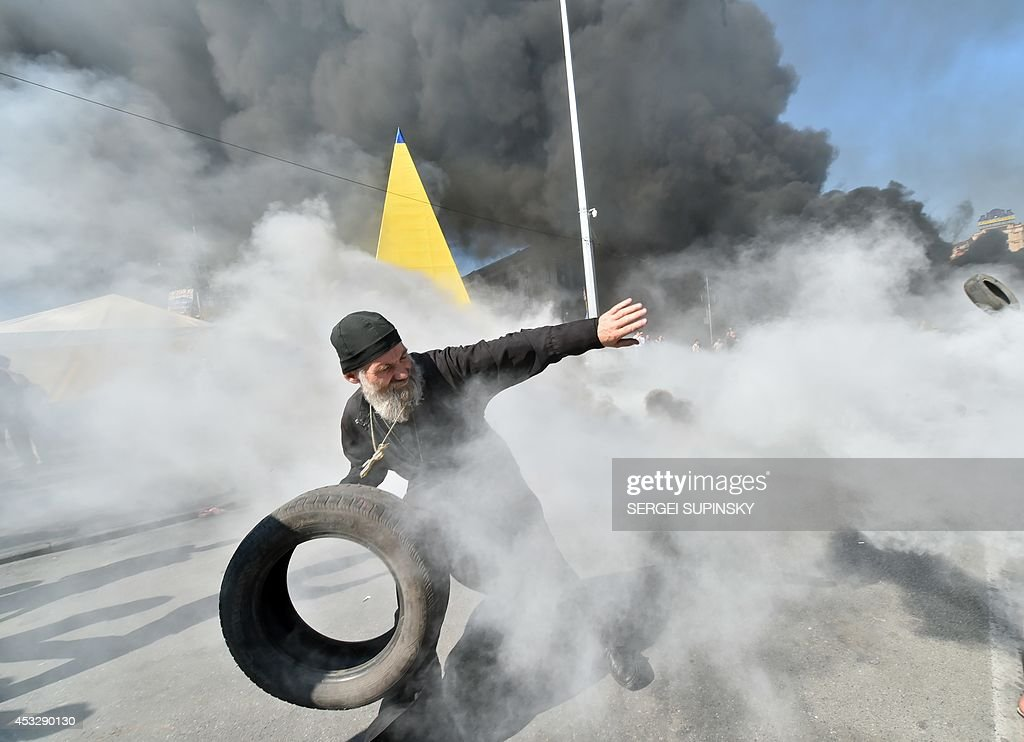 An Orthodox priest throws a tyre as Maidan selfdefence activists clash with fighters of Kiev1 volunteer battalion on Independence Square in Kiev on...