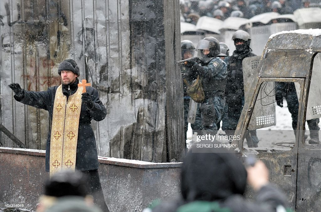 An Orthodox priest tries to stop clash protesters the police in the center of Kiev on January 22 2014 Ukrainian police on Wednesday stormed...