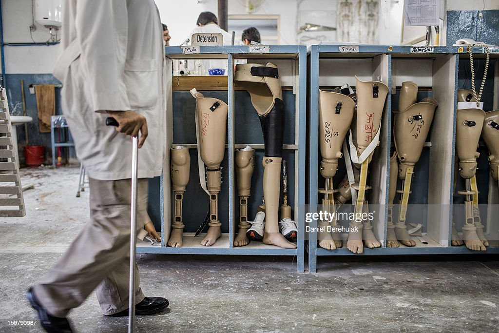 An orthopedic technician walks past prosthetic limbs being stored for patients at the International Committee of the Red Cross (ICRC), orthopedic centre on November 20, 2012 in Kabul, Afghanistan. The ICRC rehabilitation centre works to educate and rehabilitate land-mine victims, and those with limb related deformities, back into society and employment offering micro-credit financing, home schooling and vocational training to patients. The clinic itself is unique in that all of the workers are handicapped. The ICRC centre in Kabul has registered over 57,000 patients and 114,000 countrywide in all of their centres since its inception 25 years ago.