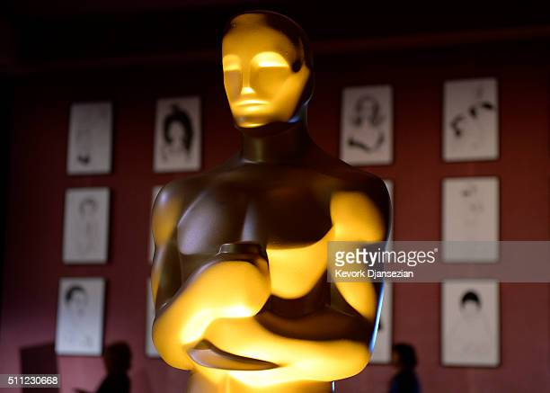 An Oscar statuette stands in front of a wall inspired by caricaturefilled wall of the iconic Sardi's and Brown Derby restaurants which will feature...