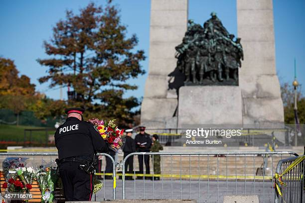 An Ottawa police officer lays flowers and pays his respects for Cpl Nathan Cirillo of the Canadian Army Reserves at the National War Memorial who was...