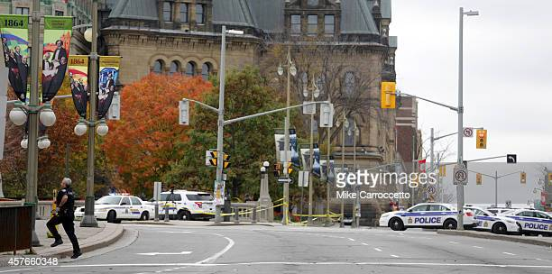An Ottawa police officer runs across Wellington St after a shooting occurred at the National War Memorial near the Canadian Parliament October 22...