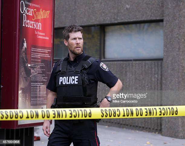 An Ottawa police officer stands guard on Elgin St in downtown October 22 2014 in Ottawa Canada Officials are investigating multiple reports of...
