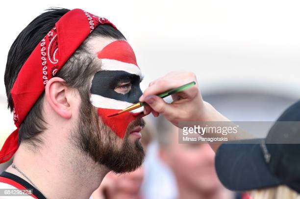 An Ottawa Senators fan gets his face painted prior to Game Three of the Eastern Conference Final between the Pittsburgh Penguins and the Ottawa...