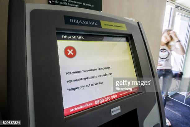 An 'out of service' notice sits on the screen of an automated teller machine inside a JSC Oshchadbank branch after the state bank was infected by the...