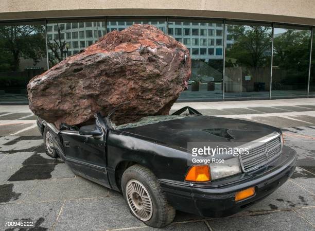 An outdoor art installation at the Smithsonian's Hirshorn Museum features a 1992 Dodge Spirit automobile crushed under a nineton volcanic boulder is...