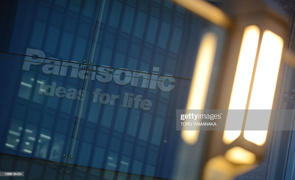 An outdoor lamp is illuminated near a logo of Japan's Panasonic at its head office in Tokyo on November 22, 2012. Fitch on November 22 dealt another blow to the Japan's embattled electronics sector, cutting its credit rating on industry titans Panasonic and Sony to junk status. AFP PHOTO/Toru YAMANAKA