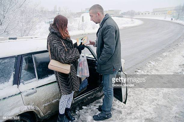 An outreach worker from a Crimean nongovernmental organisation called Hope and Salvation talks to a woman who is selling sex at the side of the road...