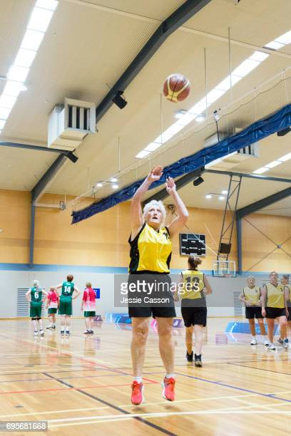 An over 60's female basketball player jumps and throws the ball