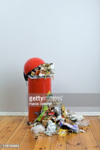An overflowing garbage can of rotting food and recyclables