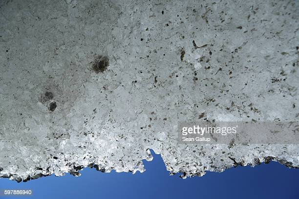 An overhang of ice melts under sunlight at the bottom of the Rhone glacier on August 22 2016 near Gletsch Switzerland In the last 120 years the Rhone...