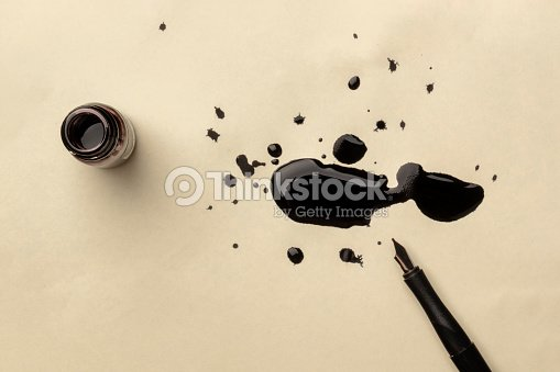 An overhead photo of an ink well with drops of ink and a nib pen, with copy space : Stock Photo