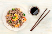 An overhead photo of soba, buckwheat noodles, with shrimps and vegetables, with chopsticks and soy sauce, shot from above on a light background