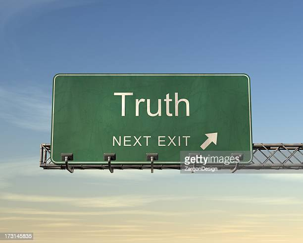 An overhead road sign in green of the word Truth