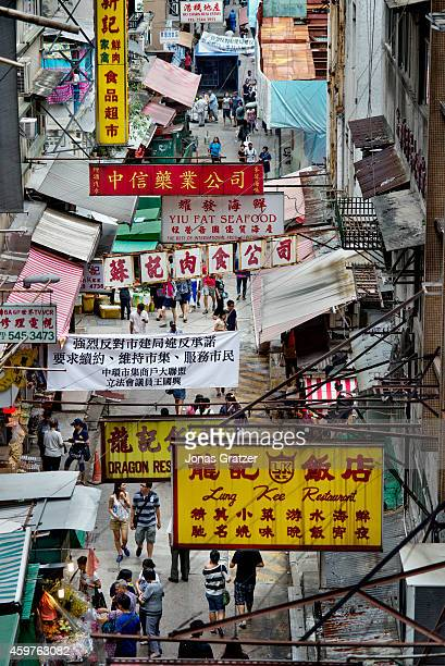 An overhead view of a street market that is crowded with signs and billboards in the city of Hong Kong