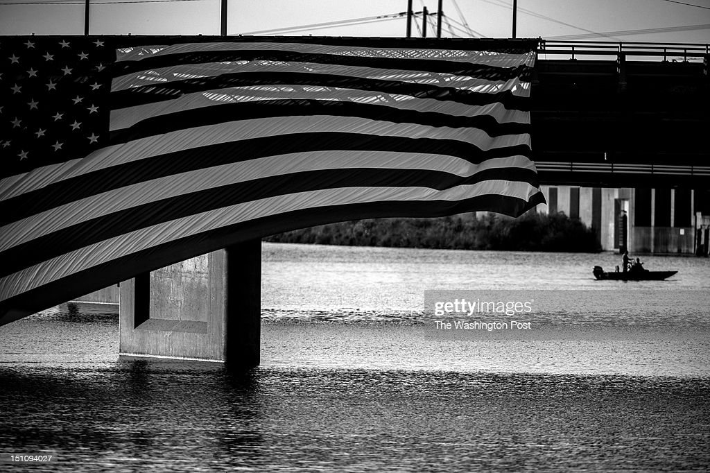 AUGUST 14 -- An oversized American flag flutters in the wind as members of the secret service detail patrol the Cedar River before President Barack Obama's arrival for a campaign stop at RiverLoop Amphitheatre, Waterloo Center for the Arts in Waterloo, Iowa, on Tuesday, August 14, 2012.