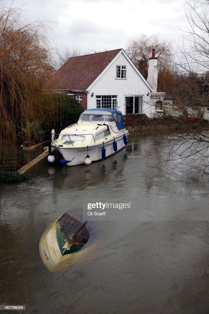 An overturned boat is surrounded by high flood water from the river Thames on January 15, 2014 near Shepperton, England. The Environment Agency has recorded a 10-year high for the water level on several stretches of the river Thames.