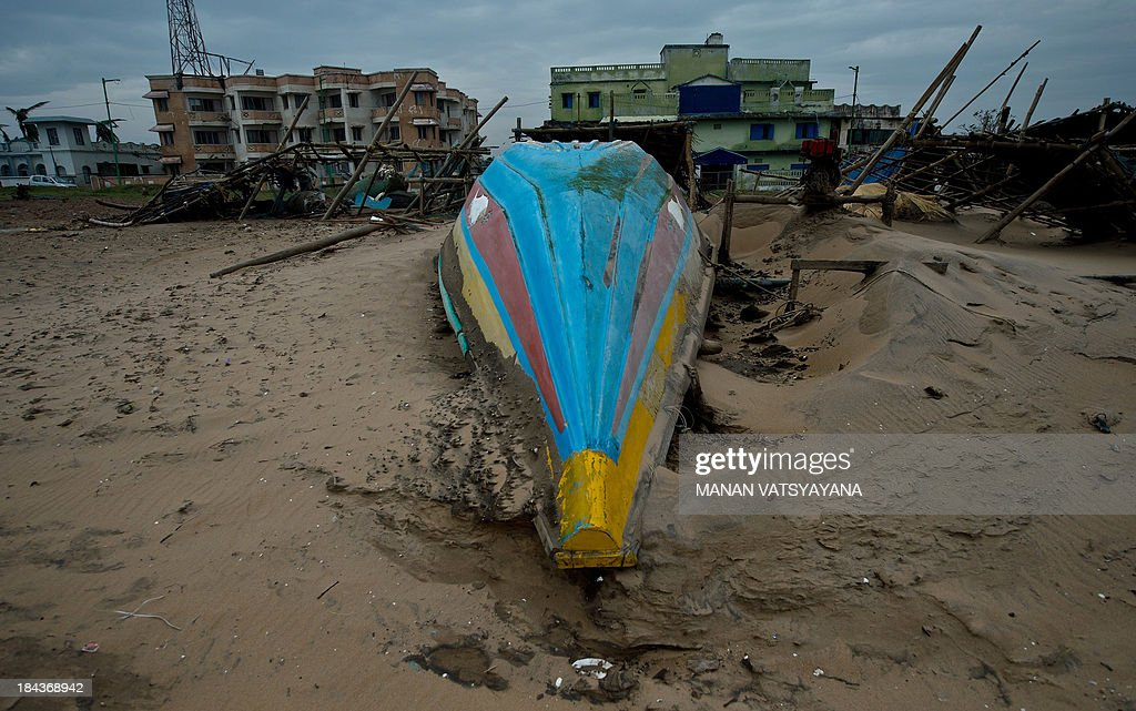 An overturned fishing boat is seen at the Gopalpur beach on October 13, 2013. Cyclone Phailin left a trail of destruction along India's east coast and up to seven people dead after the biggest evacuation in the country's history helped minimise casualties.
