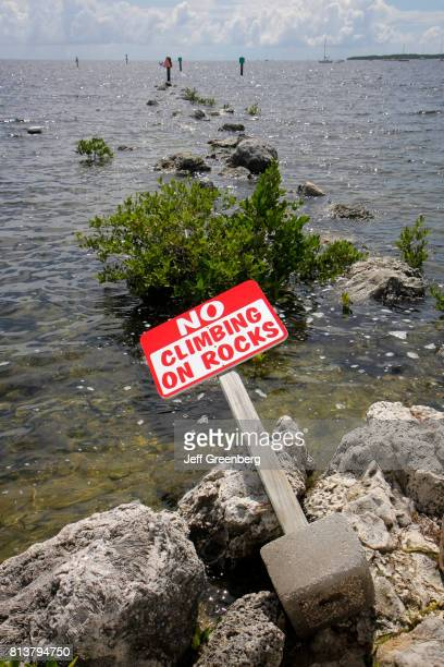 An overturned no climbing on rocks sign at Florida Bay