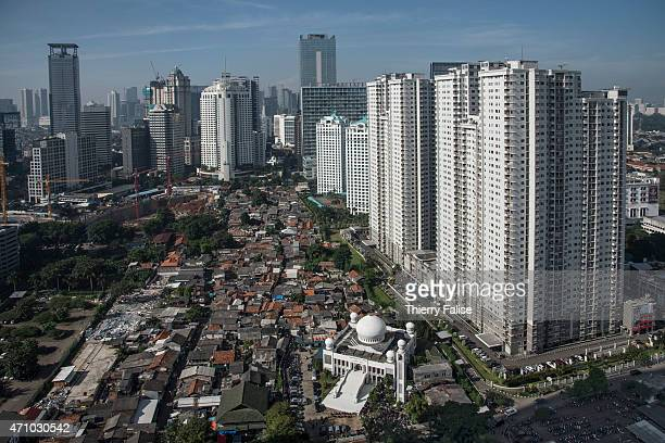 An overview of central Jakarta with a mosque skyscrapers and a shanty town