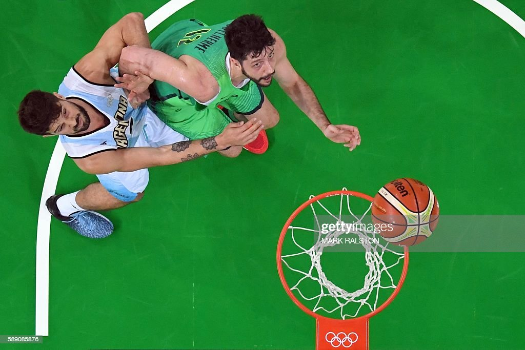 An overview shows Argentina's point guard Nicolas Laprovittola and Brazil's power forward Guilherme Giovannoni eye a rebound during a Men's round...