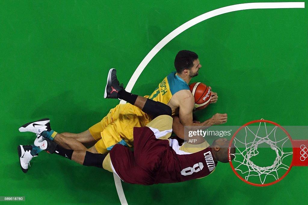 An overview shows Australia's guard Kevin Lisch and Venezuela's point guard David Cubillan fall during a Men's round Group A basketball match between...