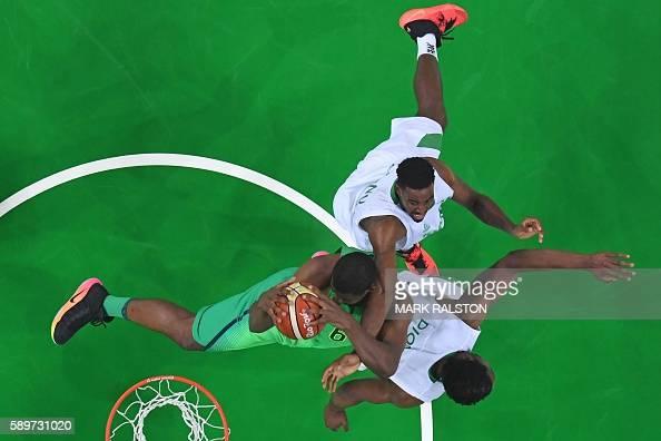 An overview shows Brazil's centre Cristiano Felicio Nigeria's power forward Ike Diogu and Nigeria's power forward Alade Aminu go for a rebound during...