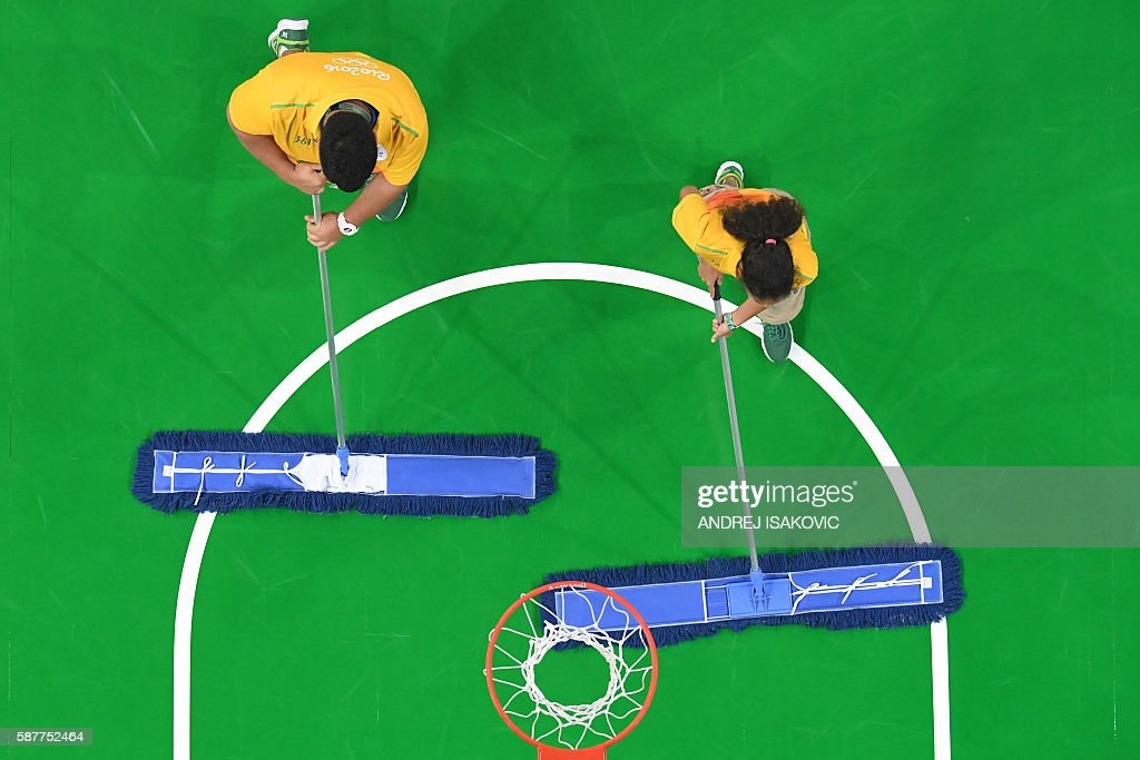 TOPSHOT An overview shows cleaners wiping the surface of the court before the fourth quarter during a Men's round Group B basketball match between...