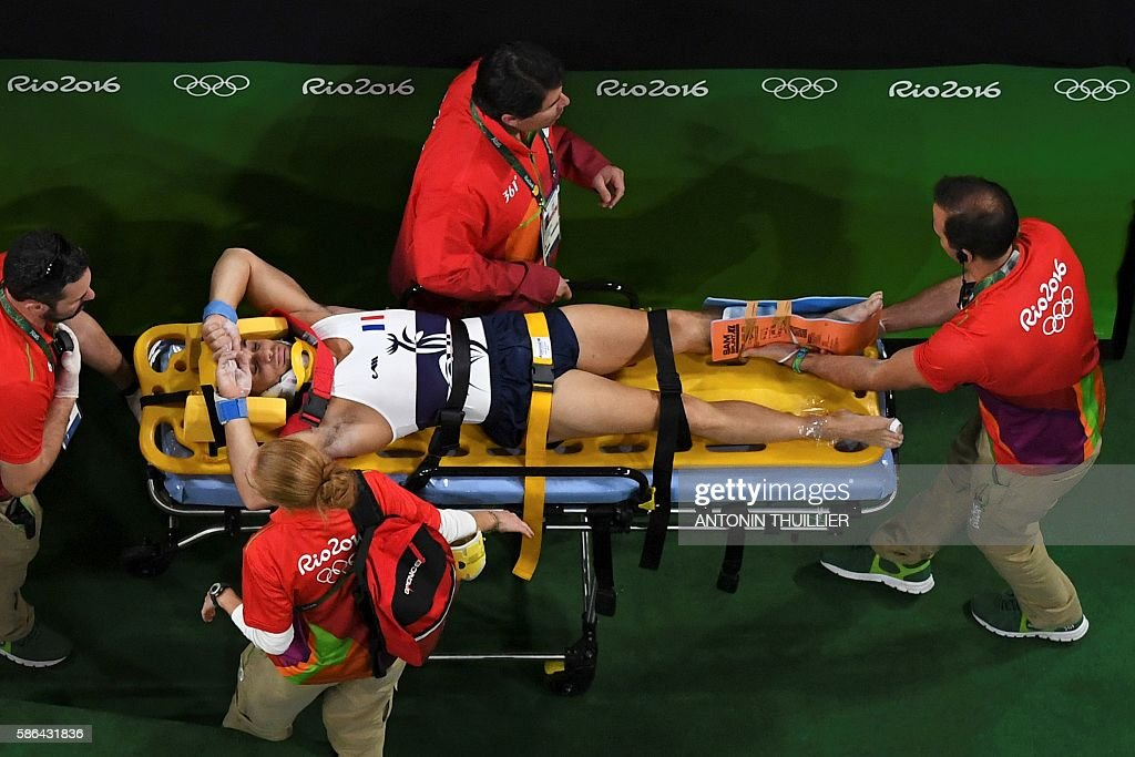 TOPSHOT - An overview shows France's Samir Ait Said being stretchered off after being injured while competing in the qualifying for the men's vault event of the Artistic Gymnastics at the Olympic Arena during the Rio 2016 Olympic Games in Rio de Janeiro on August 6, 2016. / AFP / Antonin THUILLIER