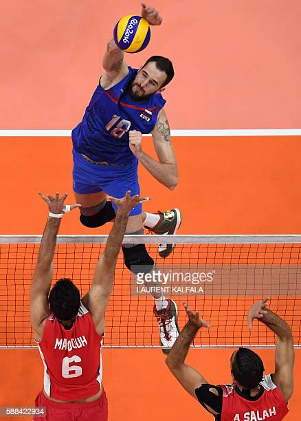 An overview shows Russia's Alexander Volkov spiking the ball during the men's qualifying volleyball match between Russia and Egypt at the...