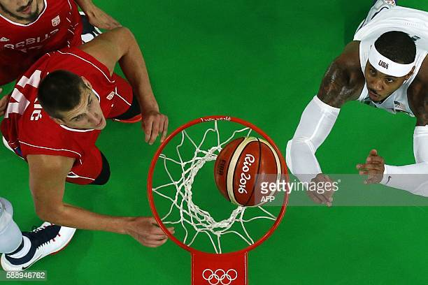 An overview shows Serbia's power forward Nikola Jokic and USA's forward Carmelo Anthony eye a rebound during a Men's round Group A basketball match...