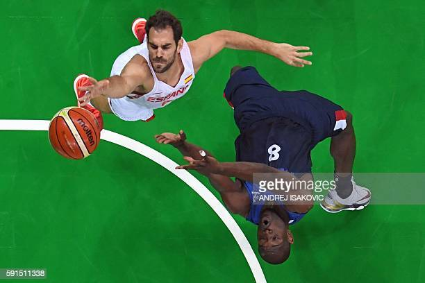 An overview shows Spain's point guard Jose Manuel Calderon go to the basket past France's small forward Charles Kahudi during a Men's quarterfinal...