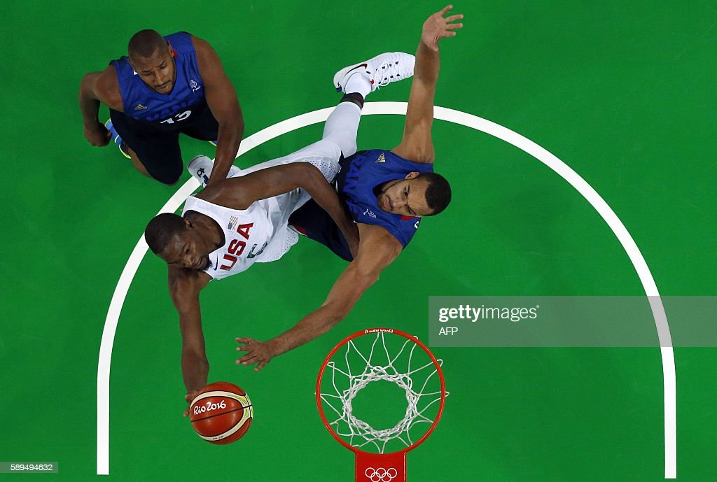 An overview shows USA's guard Kevin Durant go to the basket between France's power forward Boris Diaw and France's centre Rudy Gobert during a Men's...