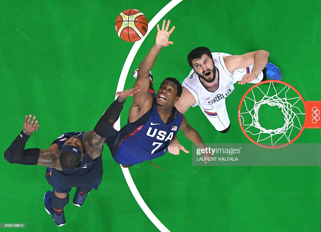 An overview shows USA's guard Kyle Lowry and USA's forward Carmelo Anthony jumping for the ball by Serbia's point guard Stefan Markovic during a...