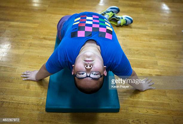An overweight Chinese student stretches during training at a camp held for overweight children at a local university on July 16 2014 in Beijing China...