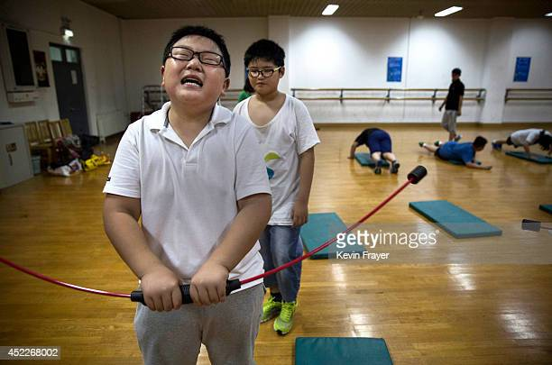An overweight Chinese student uses a strengthening device during training at a camp held for overweight children at a local university on July 16...