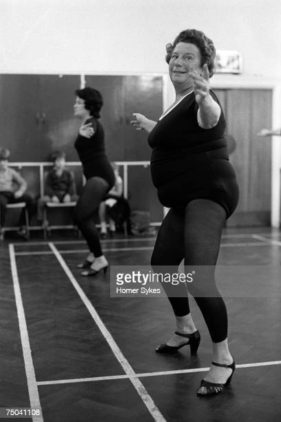 An overweight grandmother wearing high heel shoes in a keep fit dance class while exercising to pop music Essex circa 1980 Her daughter and...