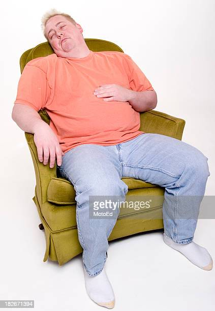 An overweight man sleeping in a chair with his shoes off