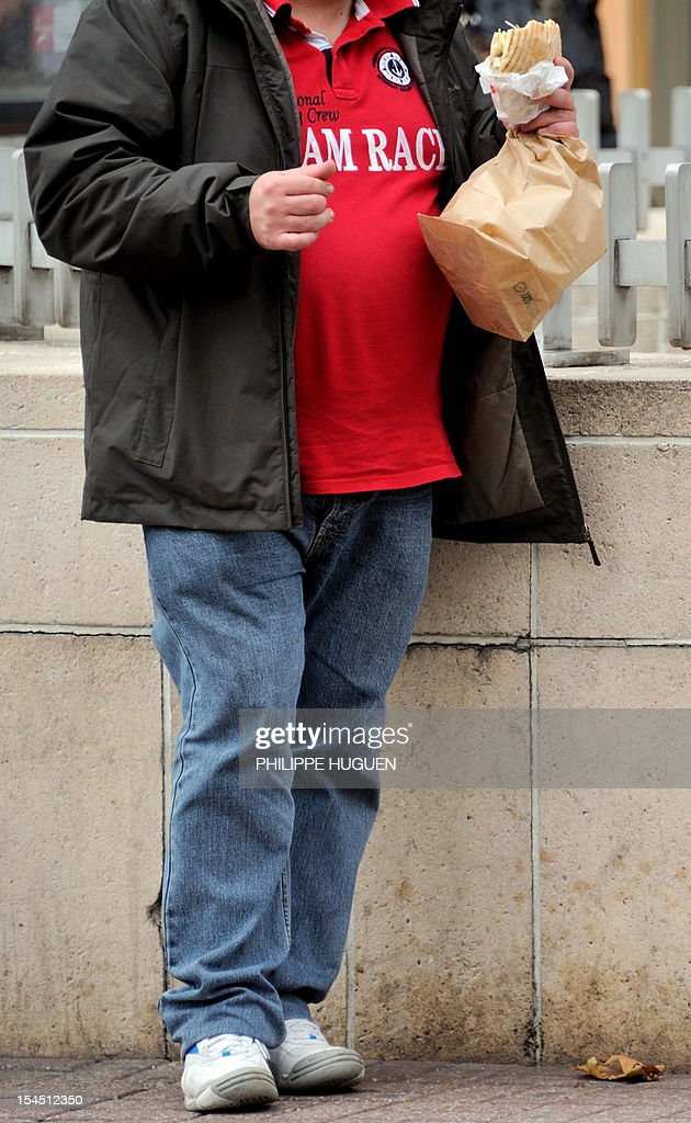 An overweight person eats in a street of the northern city of Lille on October 19, 2012.