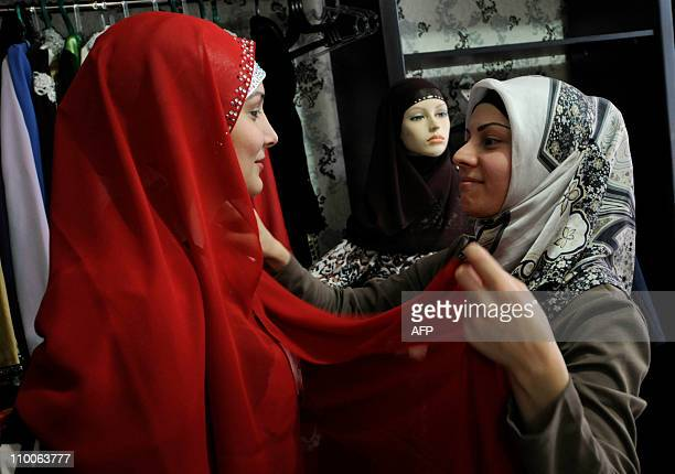 An owner and fashion designer Fatima Tisaeva helps a customer to try a traditional muslim kerchief in her readymade clothes shop 'Tesmila' in Grozny...
