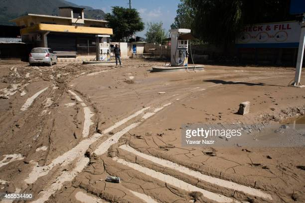 An owner looks at his silt covered gas station after the flood waters receded on September 16 2014 in Srinagar the summer capital of Indian...