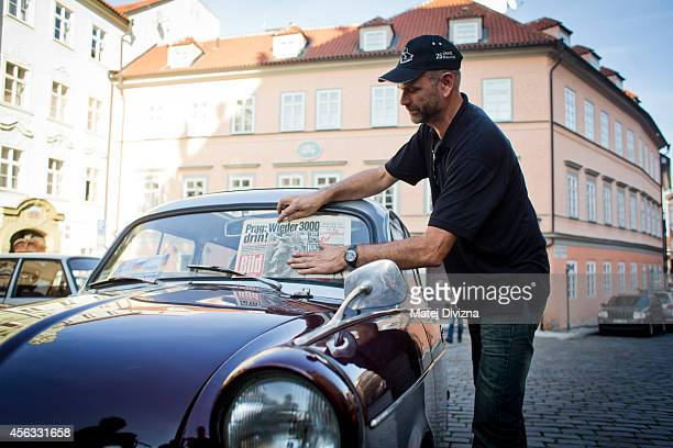 An owner places an authentic issue of German Bild newspaper from 1989 on his Trabantbrand car as he arrives at a commemoration event to the 25th...