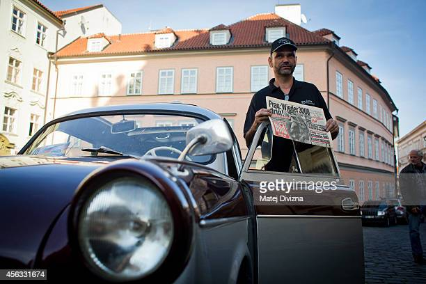 An owner poses with an authentic issue of German Bild newspaper from 1989 by his Trabantbrand car as he arrives at a commemoration event to the 25th...