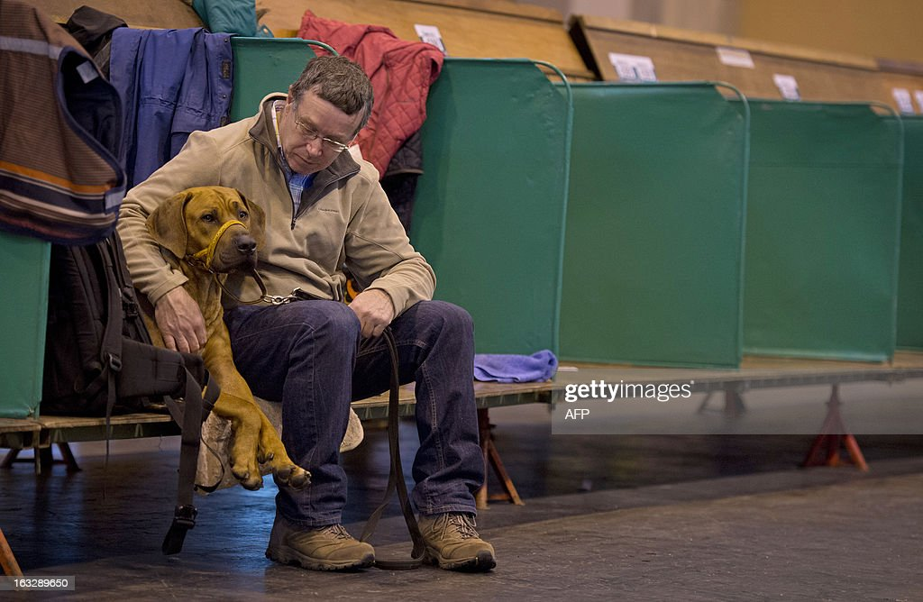 An owner sits with his dog during the first day of the Crufts dog show in Birmingham, in central England on March 7, 2013. The annual event sees dog breeders from around the world compete in a number of competitions with one dog going on to win the 'Best in Show' category.